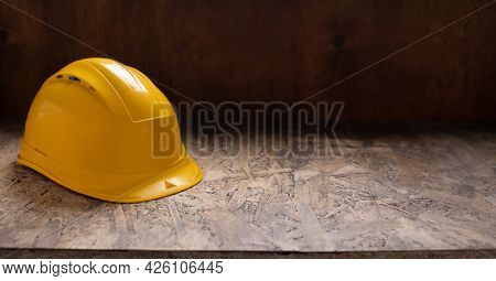 Construction helmet at wooden table background texture. Work cap on tabletop concept of repair