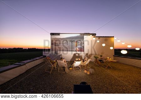 Small Group Of People Watching Movie On The Rooftop Terrace At Sunset. Open Air Cinema Concept. Roma