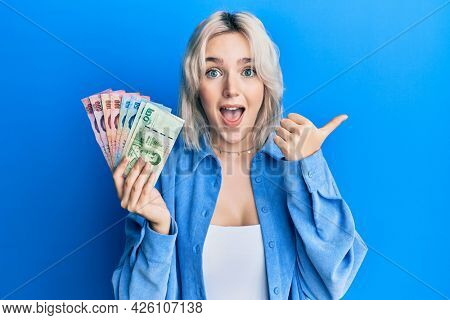 Young blonde girl holding thai baht banknotes pointing thumb up to the side smiling happy with open mouth