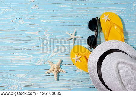 Yellow Rubber Flip Flops, White Beach Hat, Starfish On A Blue Wooden Background