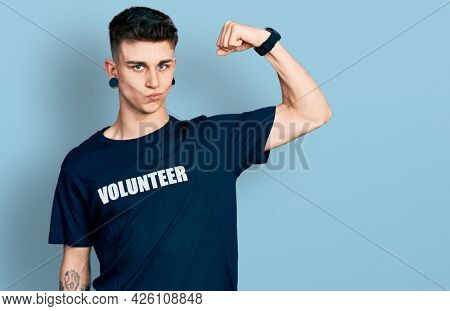 Young caucasian boy with ears dilation wearing volunteer t shirt strong person showing arm muscle, confident and proud of power