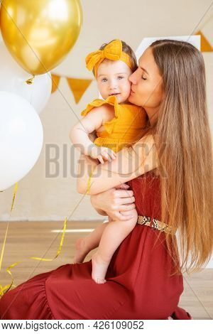 Happy Mom Kisses Her One-year-old Daughter In Yellow Clothes, Studio Photo For A Year Of The Child