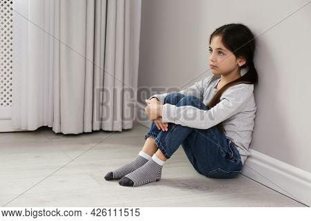 Sad Little Girl Sitting On Floor Indoors, Space For Text