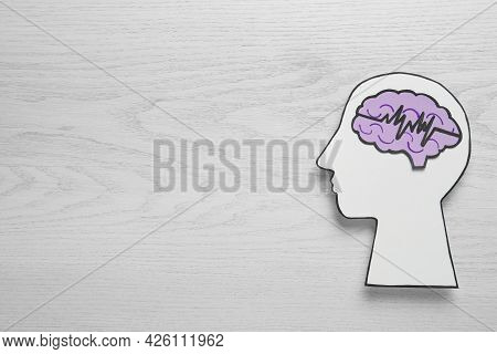 Top View Of Human Head Cutout With Brain And Pulse Line On White Wooden Background, Space For Text.