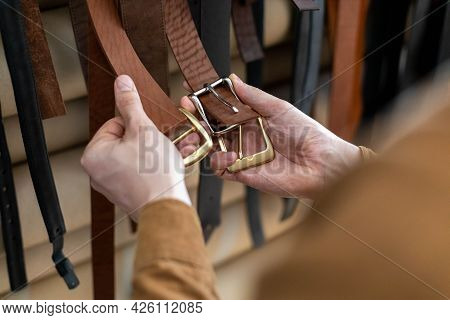 Closeup Hands Of Professional Tanner Choosing Belt Buckle On Wooden Table At Leather Workshop