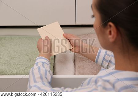 Woman Putting Scented Sachet Into Drawer With Towels