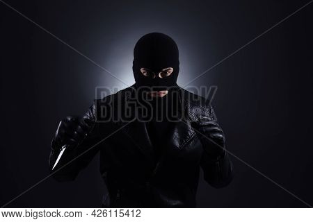 Man Wearing Knitted Balaclava With Knife On Black Background