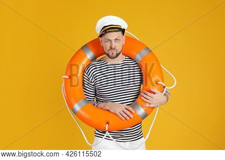 Serious Sailor With Orange Ring Buoy On Yellow Background