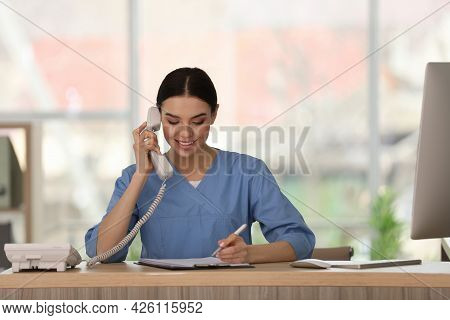 Receptionist Talking On Phone At Countertop In Hospital