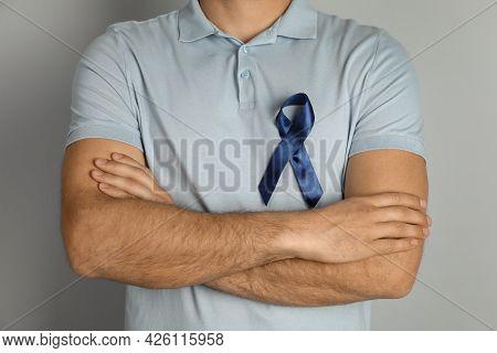 Man With Blue Ribbon On Grey Background, Closeup. Urology Cancer Awareness