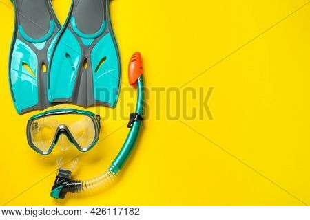 Pair Of Turquoise Flippers And Mask On Yellow Background, Flat Lay. Space For Text