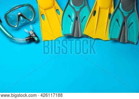 Different Flippers And Mask On Light Blue Background, Flat Lay. Space For Text