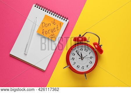 Alarm Clock, Pen, Notebook And Reminder Note With Phrase Don't Forget On Color Background, Flat Lay