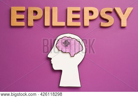 Human Head Cutout With Brain Near Word Epilepsy Made Of Wooden Letters On Purple Background, Flat La