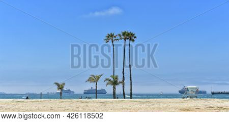 LONG BEACH, CALIFORNIA - 5 JULY 2021: Belmont Shore Beach with Crusie Ships, Sail Boats and people on the sand.