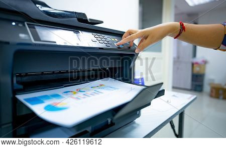 Office Worker Prints Paper On Multifunction Laser Printer. Copy, Print, Scan, And Fax Machine In Off