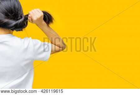 Back View Of Asian Woman Holding Damaged Hair On Yellow Background. Hair Loss And Thin Hair Problem