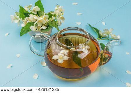 An Open Teapot With Floral Tea On A Blue Background. An Invigorating Drink That Is Good For Your Hea