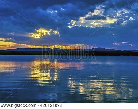 Blue Sunset Sky Over The Lake With Light Smoky Clouds Over The Horizon