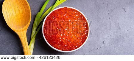 Red Caviar In A Wooden Cup On A Gray Background With A Spoon And Green Onions. A Large Pile Of Brigh