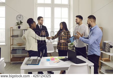Happy Diverse Business Teams Making A Deal And Shaking Hands In An Office Meeting