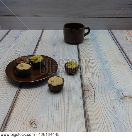 On A Wooden Table Are A Brown Porcelain Saucer And A Cup. On And Next To The Plate Are Chocolates Wi