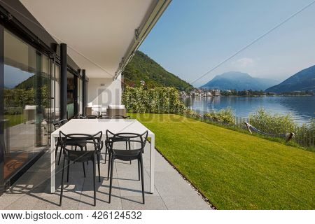 Modern house of two apartments with a beautiful garden directly on Lake Ceresio. Sunny day with blue sky. Minimalist and linear architecture. Panoramic view of the lake. Space for your text