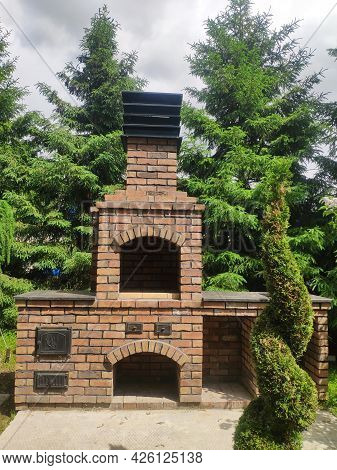 Brick Outdoor Barbecue Oven In The Garden. Stone Garden Oven For Grill In A Backyard