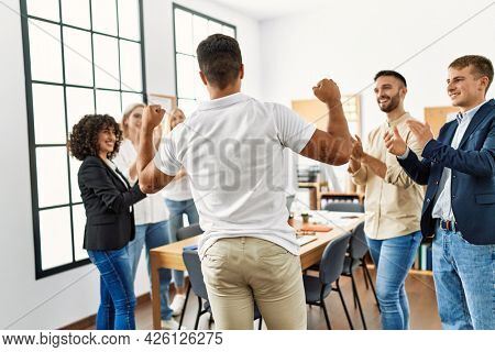 Group of young business workers smiling and clapping. Young businessman doing strong gesture with arms on back view at the office.