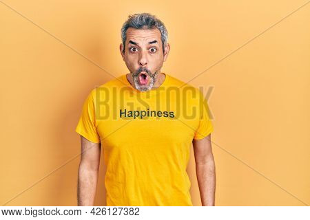 Handsome middle age man with grey hair wearing t shirt with happiness word message scared and amazed with open mouth for surprise, disbelief face