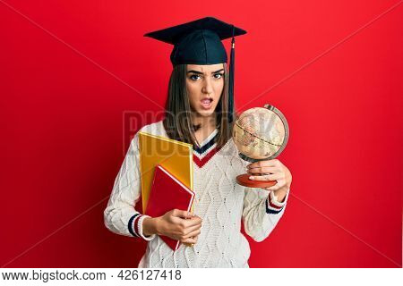 Young brunette girl graduated on geography in shock face, looking skeptical and sarcastic, surprised with open mouth