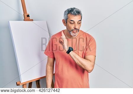 Handsome middle age man with grey hair standing by painter easel stand hand on mouth telling secret rumor, whispering malicious talk conversation