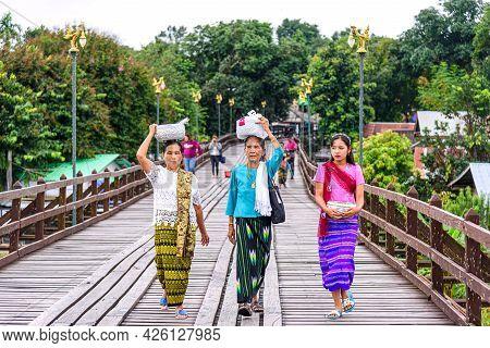 Mon Ethnic Woman Walking And Carrying Stuffs On Her Head Walk In Wooden Mon Bridge In Mon Village, S