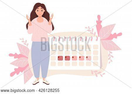 The Girl Looks At Calendar. Woman Stands Near Next To Her Menstruation Calendar. Raised Her Hands An