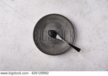 Empty Plate And Spoon. Dark Kitchen Utensils Set On Light Gray Table. Top View Flat Lay With Copy Sp