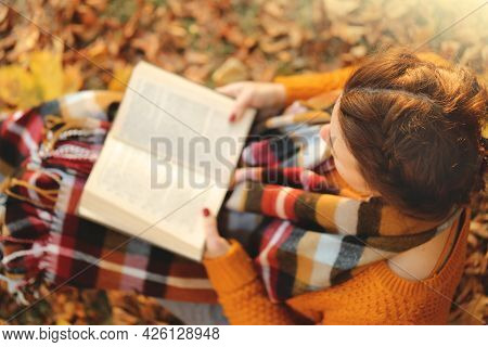 Reading Books. Learning And Knowledge. A Girl With An Open Book In Her Hands In An Autumn Garden In