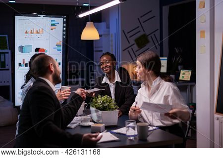 Diverse Multi-ethnic Businesspeople Overworking Late At Night Analyzing Management Ideas Solving Com
