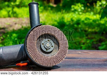 Grinder On A Wooden Table. Abrasive Wheel On An Angle Grinder.