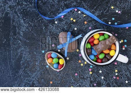 Various Chocolate Candies In White Mug On Black Texture Background. Egg-shaped Sweets And Chocolate