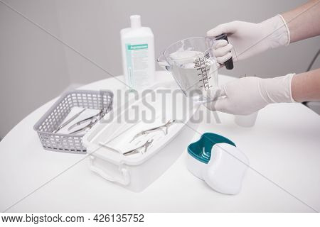 Manicurist Pouring Liquid Sterilizer Into Container With Nail Nippers