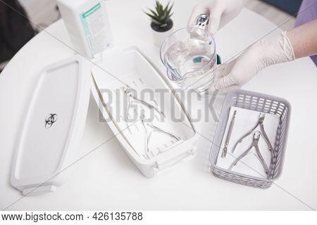 Unrecognizable Manicurist Sterilizing Her Tools In Disinfectant Liquid