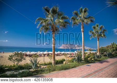 Turkey, Alanya - October 20, 2020: Alanya promenade - Ahmet Tokus Boulevard along all Beaches. Tourists promenade along the alley along the Mediterranean coast. Alanya, Turkey