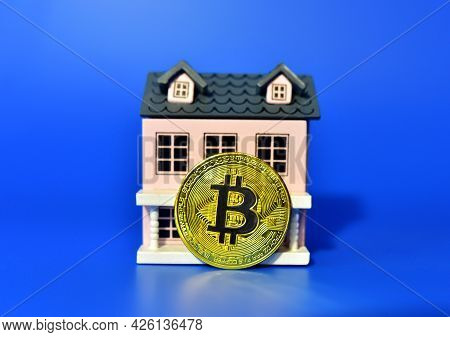 Bitcoin Coin On The Background Of A Wooden House. The Concept Of Buying Real Estate And Housing For