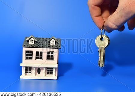 Miniature House And Keys In Hand On Blue Background. Home Buying Or Selling. Miniature Home For Fami
