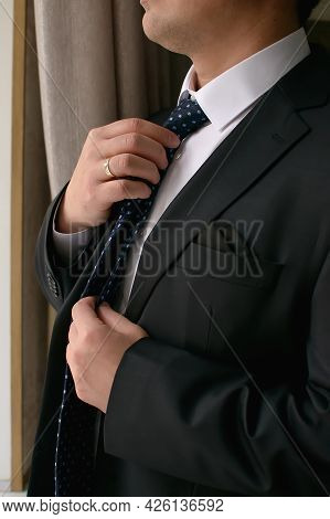 Groom In A Black Suit Adjusts His Tie Looking To The Side In Close-up