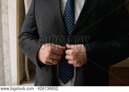 Groom In A Black Suit With A Tie Fastens A Button On His Suit Close-up