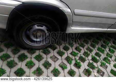 Wheel On Eco Friendly Parking Lot With Grass Germination With Copy Space. Eco Car Parking Of Concret