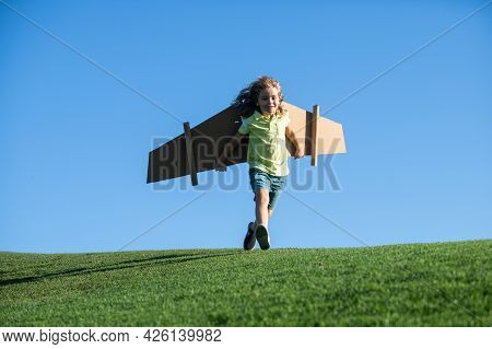 Child Boy Playing Pilot On The Sky Blue Background. Kid Dreaming. Child Playing With Toy Jetpack. Ki