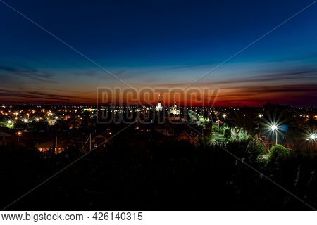 Evening Panorama Of The City On The Background Of Sunset With A Blue-maroon Sky.the Horizon Line At