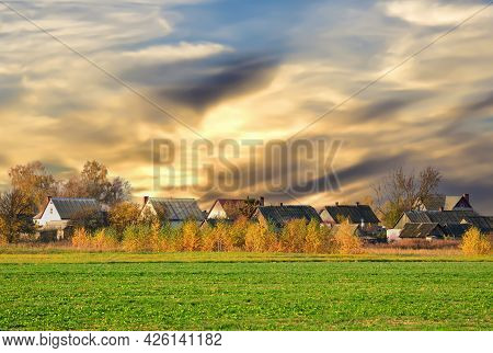 View Of The Green Field With Homes In The Distance And Farm Buildings In Forest On Sunset Background